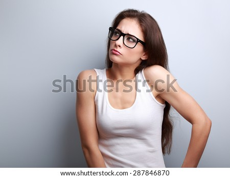 Anger young casual woman in glasses thinking and looking up on blue background with empty copy space - stock photo
