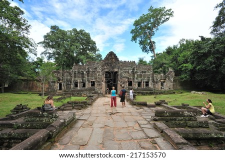 ANGKOR - AUG 14: Tourists visit a temple at the historic Angkor complex on Aug 14, 2013 in Angkor, Cambodia. The UNESCO world heritage site attracted 1.12 mln visitors in the first half of 2013. - stock photo