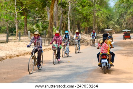 ANGKOR, CAMBODIA - FEB 21, 2013: Unidentified local women and other people ride bicycles and motorbikes at Angkor complex, the prime countrys attraction for tourists. - stock photo