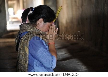 ANGKOR - JULY 11: An unidentified woman prays in a Buddhist merit making ceremony at Angkor Wat on July 11, 2012 in Angkor, Cambodia. Theravada Buddhism is practiced by over 95% of Cambodians. - stock photo
