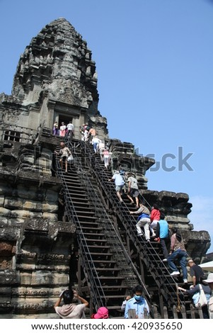 ANGKOR WAT, CAMBODIA - JANUARY 29, 2015: Unidentified tourists at temple in Angkor Wat. Angkor Wat is the largest Hindu temple complex and religious monument in the world.