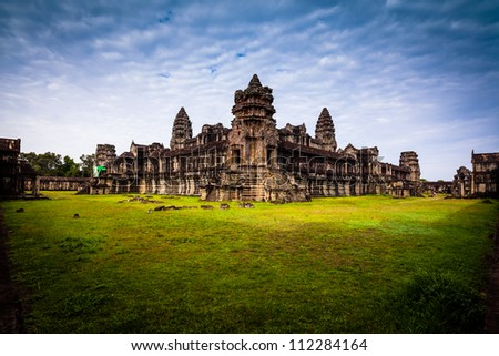 Angkor wat from the back wall with green grass and blue sky - stock photo