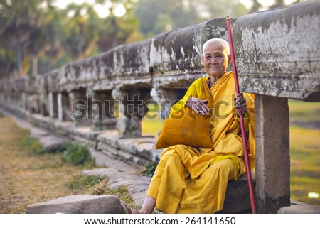 ANGKOR WAT, KRONG SIEM REAP, SIEM REAP, CAMBODIA-JANUARY 5, 2015: An unidentified old buddhist female monk dressed in orange toga at Angkor Wat temple. - stock photo