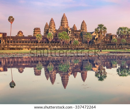 Angkor Wat temple at dramatic sunrise reflecting in water - stock photo
