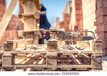 Angle grinder power tool on construction site - tools and wooden blocks at building site - stock photo