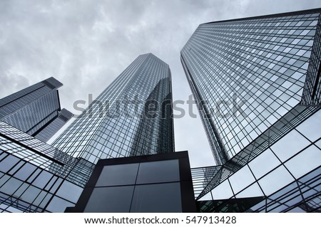 Angle shot of office buildings against a cloudy sky. Toned image