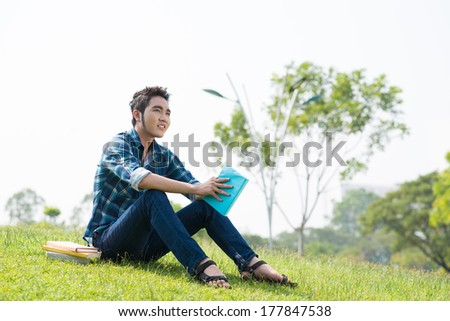 Angle view of a fashionable student with a book on the foreground  - stock photo