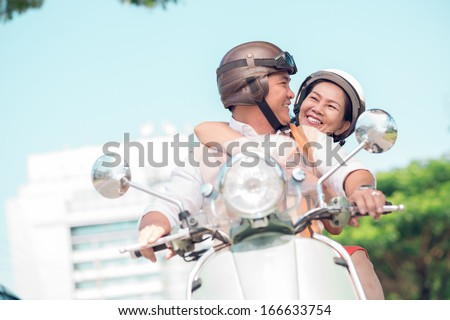 Angle view of a happy senior couple on the scooter - stock photo