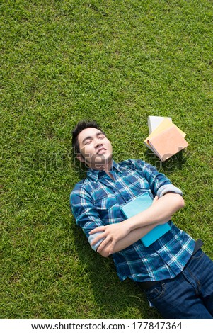Angle view of a smiling guy lying on the grass with books with closed eyes  - stock photo