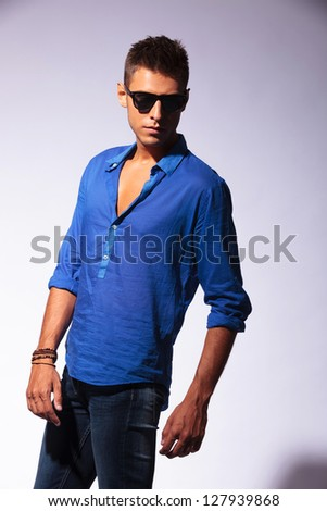 angle view of a young casual man posing on a light background, looking away from the camera