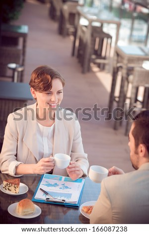 Angle view of business co-workers at a cafe during their business lunch  - stock photo