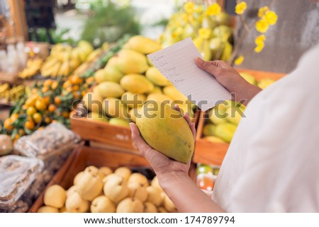 Angle view of human hands holding a shopping list while choosing a mango on the foreground  - stock photo