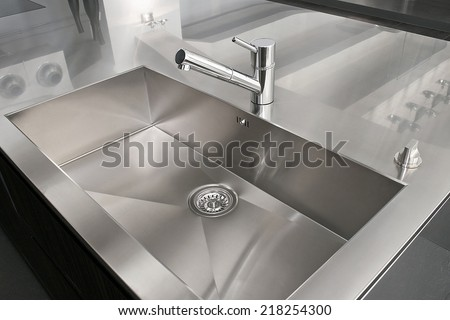 Angle view of kitchen sink with silver faucet - stock photo