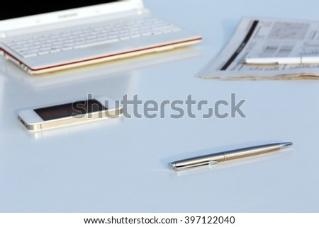 Angle View of Work Place with Laptop Pen Telephone and Business Newspaper on White Office Desk Table  - stock photo