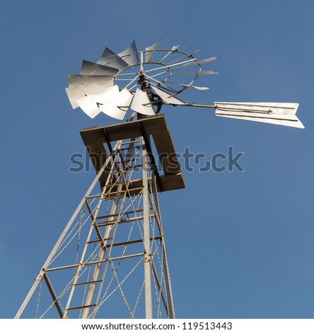 Angled and close up shot from the ground of an old fashioned power windmill against a clear blue sky.