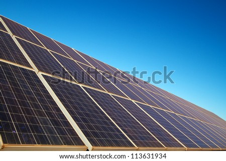 Angled close-up of solar panels, blue sky
