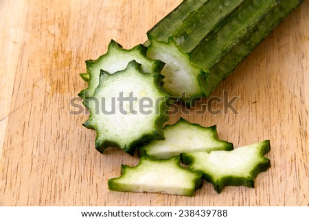 Angled Gourd or fresh loofah slice on the wooden plate - stock photo
