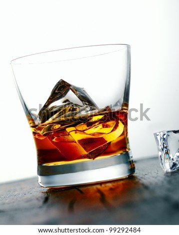 Angled image of a glass of golden whiskey or brandy on the rocks with large ice cubes served on a bar countertop - stock photo