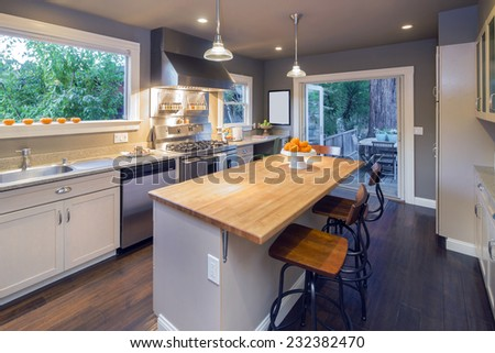 Angled photo of luxury modern styled kitchen with white wooden cabinets, stainless steel appliances, granite counter and kitchen island with wooden counter including french doors leading to outdoors.  - stock photo