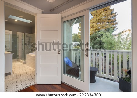 Angled photo showing luxury bathroom and and balcony with botanical garden divided by sliding french doors in luxury mansion.  - stock photo