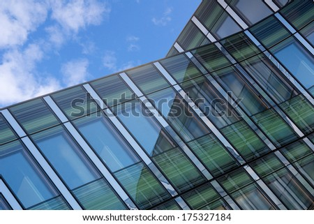 Angled shot of an office building with shiny blue glass and green facade on a sunny day