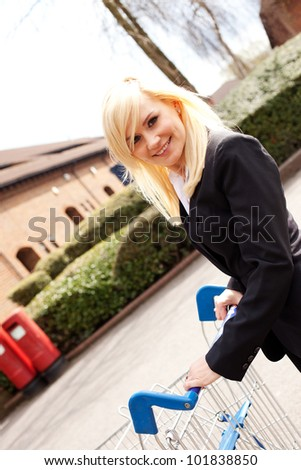 Angled view of a smiling attractive blonde woman pushing a shopping trolley across an empty carpark - stock photo