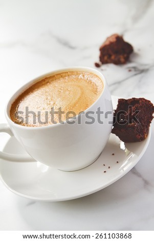 Angled view of cappuccino or latte coffee with chocolate brownie cookie on marble table - stock photo