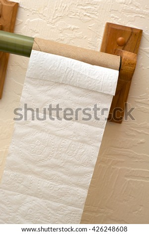Angled view of end of toilet paper roll showing cardboard roll on wooden holder. - stock photo