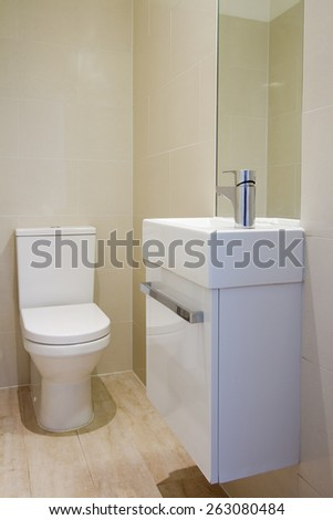 Angled view of newly renovated fully tiled bathroom toilet and basin - stock photo