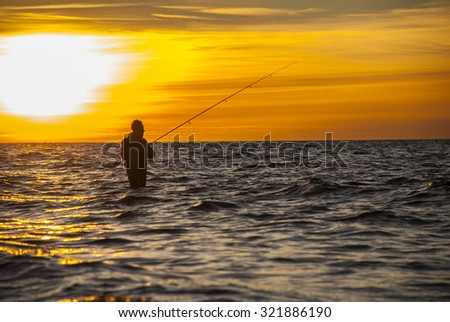 Angler fishing at the coast in Autumn sunset