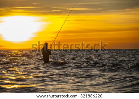 Angler fishing at the coast in Autumn sunset - stock photo