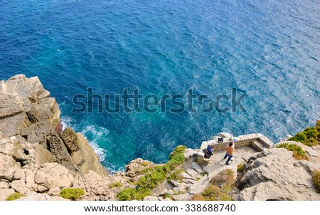 Angler fishing from the rocks near Peniche (Portugal). A view from above. Selective focus on the man.  - stock photo