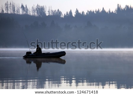 Angler fishing on the lake on a misty morning - stock photo