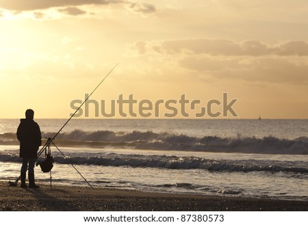 Angler on deserted beach at sunset - stock photo