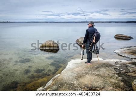 Angler on spring sea coast - stock photo