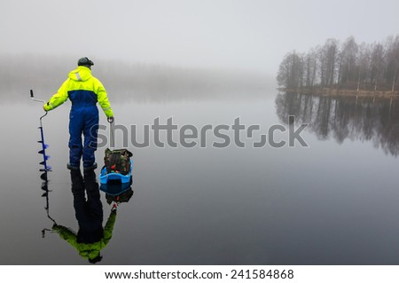 Angler with fishing equipment on the ice - stock photo