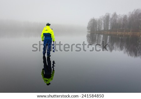 Angler with ice drill - stock photo