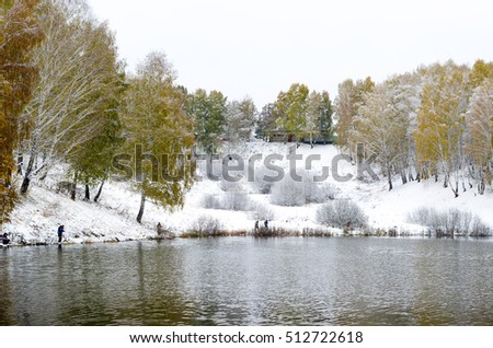 Anglers with spinning on the shore of snow lake in the distance in the bushes near the shore in frost under the yellow birches in the winter. Soft focus.