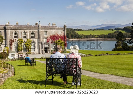 Anglesey, Wales. UK - September 8, 2015:. Retired Couple enjoying the breath taking scenic view of Plas Newydd Country House,situated on the bank of the Menai Strait with Snowdonia in the distance. - stock photo
