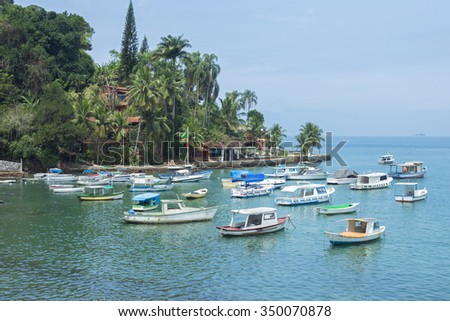 ANGRA DOS REIS, BRAZIL - OCTOBER 2, 2015: Angra dos Reis is known for it's many vibrant marinas docked with traditional boats surrounded by crystal clear waters and a lush tropical landscape. - stock photo