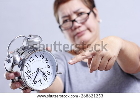 Angry adult woman pointing to a table clock.