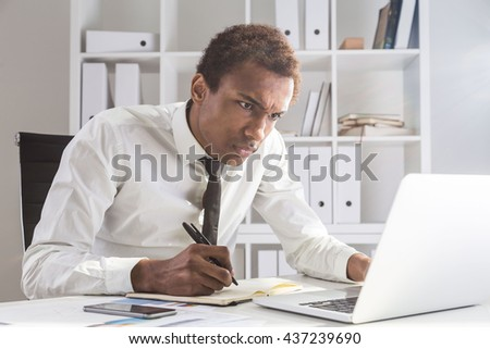 Angry african american businessman working on project at office desk with laptop, notepad and smartphone. Shelf with documents in the background - stock photo