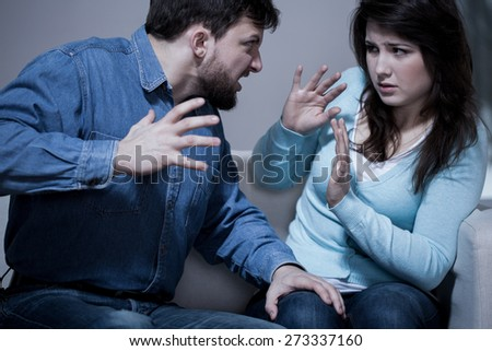 Angry aggressive husband trying to hit his wife