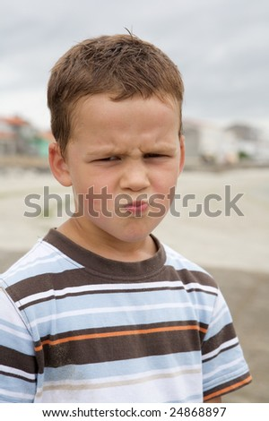 Angry and funny boy making grins outside - stock photo
