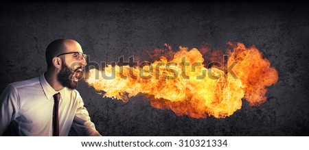 angry and furious announcement - businessman spitting fire  - stock photo