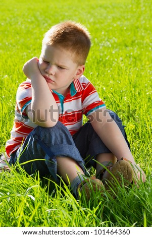 angry and  sad boy sitting on grass - stock photo