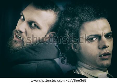 Angry and sad vampires looking camera - stock photo