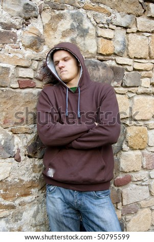 Angry and unhappy man next to brick wall