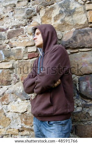 Angry and unhappy young man. In background brick wall