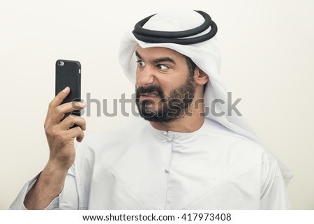Angry Arabian Businessman, Arabian Businessman expressing anger on the phone  - stock photo
